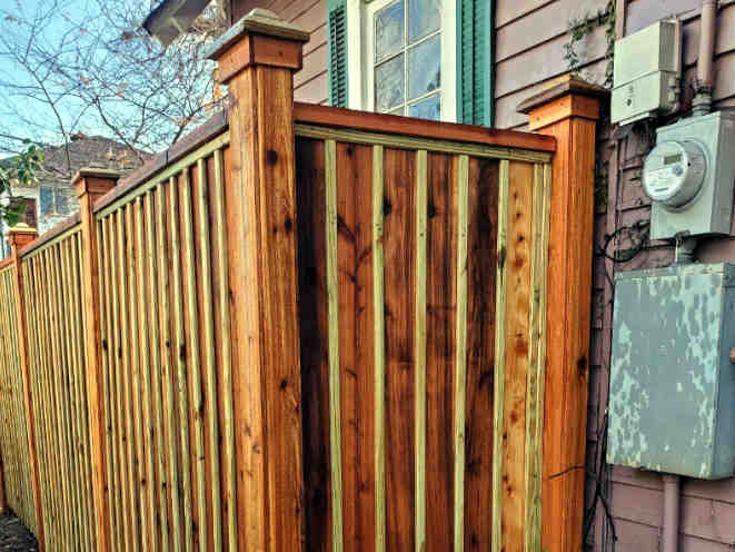Stained Custom-Built Cedar Fence with Custom Post Caps located off S. Claiborne Avenue in New Orleans.