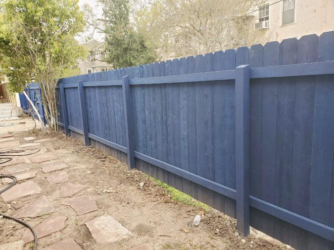 Standard six-foot-high cedar fence painted blue on Audubon Street in New Orleans.
