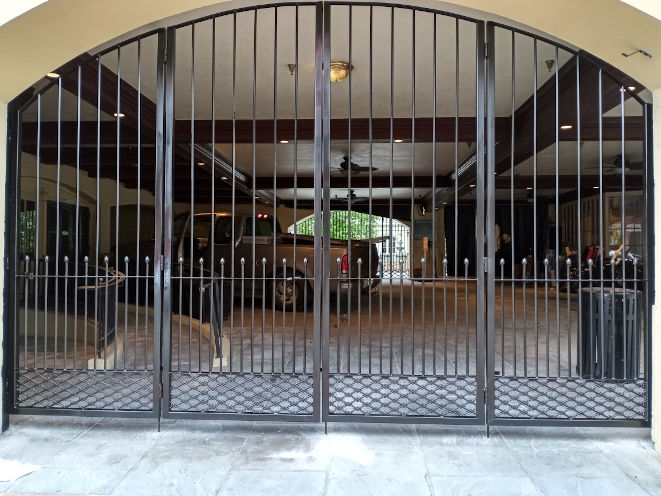 Custom iron bi-folding arched gate installed at the Maison Dupuy Hotel on Toulouse St. in New Orleans.